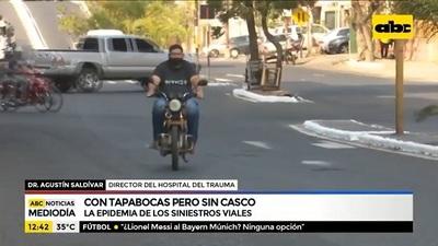 En moto, con tapabocas, pero sin casco