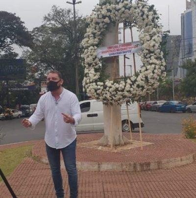 Solitario manifestante coloca corona de flores por mástil en CDE