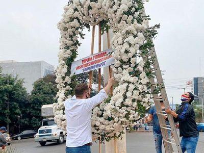 Depositan corona de flores en CDE por obras que no se hicieron