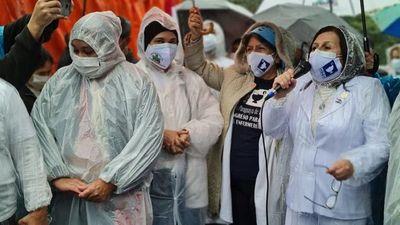 Enfermeras protestan bajo la lluvia en la víspera de su día