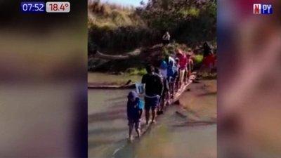 Niños indígenas deben cruzar a pie un helado arroyo para ir a clases