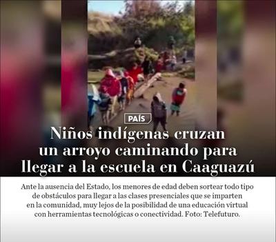 Niños indígenas cruzan un arroyo caminando para llegar a la escuela en Caaguazú