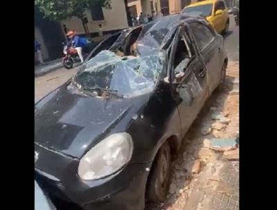 Parte de edificio se desploma y aplasta un auto en el microcentro